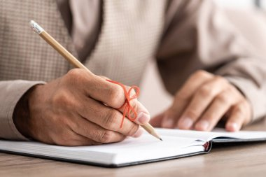 cropped view of retired man with alzheimers disease string human finger reminder writing in notebook