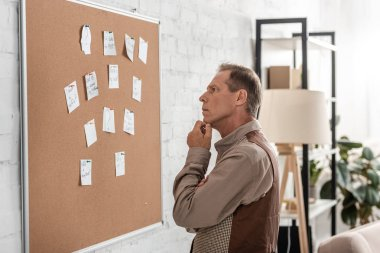 pensive retired man with alzheimer looking at board with papers