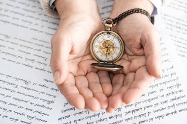 top view of senior woman holding pocket watch near papers with letters