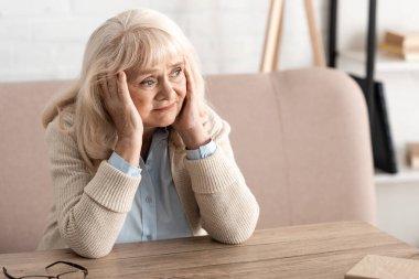 sad senior woman with memory loss at home