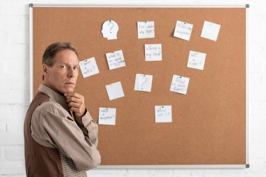 Pensive retired man standing near papers with letters on bard stock vector