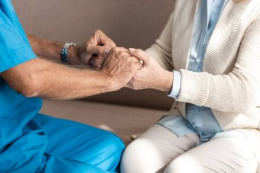 cropped view of doctor holding hands with senior woman