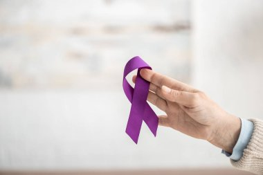 Cropped view of woman holding purple ribbon at home stock vector