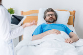 Photo cropped view of doctor holding digital tablet and patient lying in bed in hospital