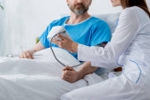 cropped view of doctor measuring blood pressure of patient in hospital