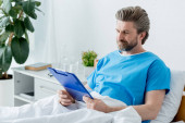 patient in medical gown looking at clipboard in hospital