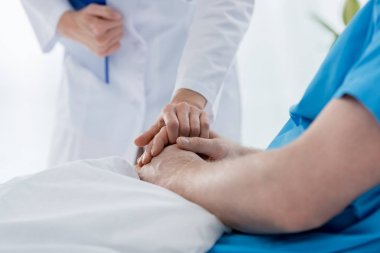 cropped view of doctor in white coat holding hand of patient in hospital