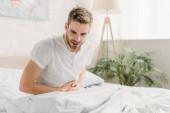 mladý muž sedí na bílém lůžku a trpí bolestí břicha
