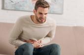 mladý muž sedí na pohovce a dotýká břicha, zatímco trpí bolestí břicha