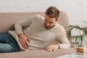 mladý muž ležící na pohovce a trpící bolestí břicha