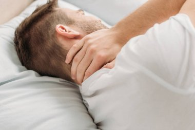 young man lying in bed and suffering from neck pain