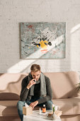 Fotografie ill man sitting on sofa near table with medicines and using nasal spray