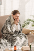 diseased woman, wrapped in blanket, sitting on sofa and sneezing in napkin