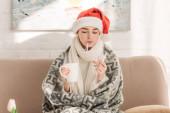 krankes Mädchen in Weihnachtsmannmütze misst Temperatur, während es Nasenspray und eine Tasse wärmenden Drink in der Hand hält
