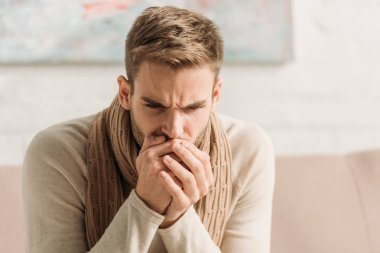 diseased man in warm scarf coughing in folded hands