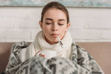 sick woman measuring temperature while holding cup of warming drink