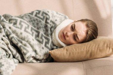 sick, upset girl lying on sofa under blanket