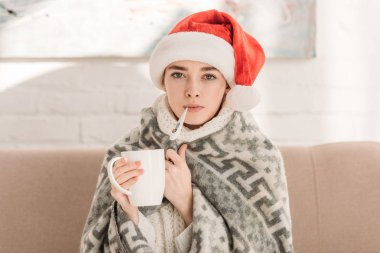 Sick girl in santa hat, wrapped in blanket, looking at camera and holding cup of tea stock vector