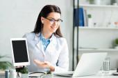 Fotografie Lächelnder Arzt zeigt Diagnose auf digitalem Tablet, während er Online-Beratung am Laptop hat