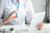 Fotografie Ausgeschnittene Ansicht des Arztes zeigt dem Patienten Pillen bei Online-Konsultation auf digitalem Tablet im Büro