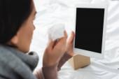 nemocná žena s ubrouskem po on-line konzultaci s lékařem na digitální tablet