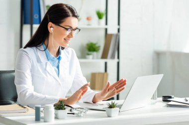 attractive smiling doctor having online consultation with patient on laptop in clinic office