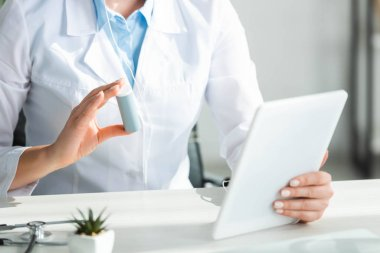 cropped view of doctor showing pills to patient on online consultation on digital tablet in office