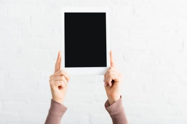 Cropped view of woman holding digital tablet with blank screen stock vector