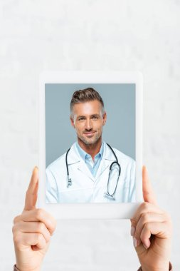 Cropped view of woman holding digital tablet with doctor on online consultation, on white stock vector