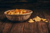 vynikající křupavé bramborové lupínky v proutěném koši na dřevěném stole