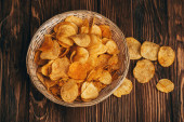 Fotografie top view of delicious crispy potato chips in wicker basket on wooden table