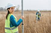 Selektivní zaměření ženského zeměměřiče s pravítkem a kolegyní s digitální úrovní v terénu