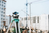 Photo Digital level on tripod with construction site on background