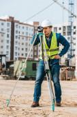 Vermessungsingenieur in Harthut und Warnweste mit digitalem Pegel auf Baustelle