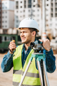 Usmívající se zemědělec s digitální úrovní mluvící na rádiu se staveništěm na pozadí