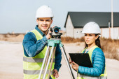 Surveyors with digital level and clipboard looking away