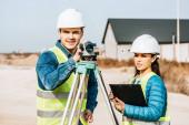 Fotografie Vermessungsingenieure mit digitalem Pegel und Klemmbrett schauen weg