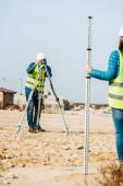 Selektivní zaměření inspektorů pracujících s pravítkem a digitální úrovní na staveništi