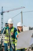 Průzkumníci s digitální úrovní při pohledu na nákres na staveništi