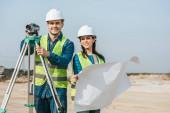 Lächelnde Vermessungsingenieure mit digitalem Pegel und Blaupause, die in die Kamera schauen