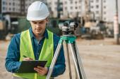 Vermessungsingenieur schreibt auf Klemmbrett neben digitaler Ebene auf Baustelle
