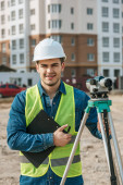 Surveyor holding clipboard and digital level and smiling at camera on construction site