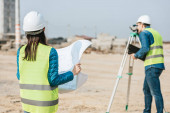 Selective focus of surveyor with blueprint and colleague using digital level on construction site