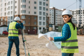 Selective focus of surveyor with blueprint smiling at camera and colleague using digital level on construction site