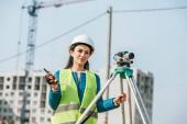 Smiling surveyor with digital level and radio set on construction site