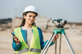 Attractive surveyor with digital level and radio set smiling at camera