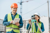 Fotografie Smiling surveyors with digital tablet and measuring level on construction site
