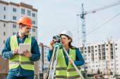 Vermessungsingenieure arbeiten mit digitalem Tablet und Füllstand auf Baustelle