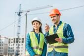 Usmívající se zeměměřič se schránkou ukazující na kolegu na staveništi
