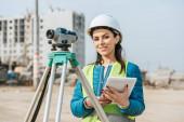 Surveyor s digitálním tabletem a měřicí úrovní usmívající se na kameru